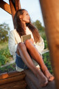 Young lady with book in summerhouse on sunset Stock Photography