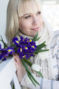Young lady with a bouquet of irises and tulips enjoying the spri Royalty Free Stock Photo