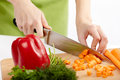 Young lady chopping vegetables hands of a woman on a wooden board Royalty Free Stock Image