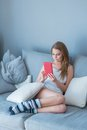 Young lady comfortably sitting on a couch while using smart tablet Stock Photography