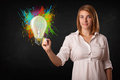 Young lady drawing a colorful light bulb with colorful splashes on white background Stock Photography