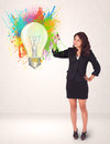 Young lady drawing a colorful light bulb with splashes on white background Royalty Free Stock Image