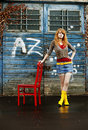 Young lady with gumboots and a red chair Stock Photo