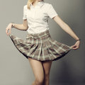 Young lady lifting up her short skirt plaid Stock Images