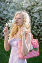 Young lady with pink bag smelling cherry flowers Royalty Free Stock Photos