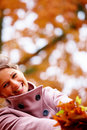 Young lady playing with maple leaves Stock Photography