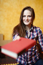 Young lady reading a book on the bed caucasian woman with long hair and plaid shirt giving to camera with selective focus Royalty Free Stock Photography