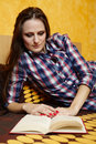 Young lady reading a book on the bed caucasian woman with long hair and plaid shirt with selective focus Royalty Free Stock Photography