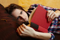 Young lady reading a book on the bed caucasian woman with long hair and plaid shirt with selective focus Stock Photos