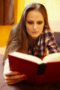 Young lady reading a book on the bed caucasian woman with long hair and plaid shirt with selective focus Royalty Free Stock Photos