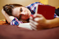 Young lady reading a book on the bed caucasian woman with long hair and plaid shirt with selective focus Royalty Free Stock Images