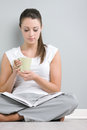 Young lady reading a book portrait of woman with holding cup of coffee or tea Stock Image