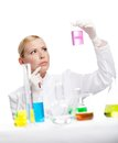 Young lady scientist stares at the beaker Royalty Free Stock Photos