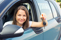 Young lady sitting in a car and showing key Royalty Free Stock Photography