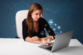 Young lady sitting at desk and typing on laptop with social netw beautiful network icons comming out Royalty Free Stock Photography