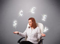 Young lady sitting and juggling with currency icons pretty Stock Photos