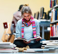 Young lady sitting and reading book in library Royalty Free Stock Photo