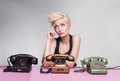 Young lady sitting and thinking on a pink desk with colorful antique phones Royalty Free Stock Images
