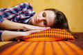 Young lady sleeping closeup of a woman on a bed with orange pattern sheets with selective focus Royalty Free Stock Image