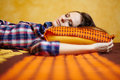 Young lady sleeping closeup of a woman on a bed with orange pattern sheets with selective focus Stock Photo