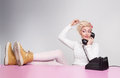 Young lady speaking on the phone while her legs on the desk Stock Images