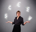 Young lady standing and juggling with currency icons pretty Stock Images