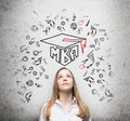Young lady is thinking about mba degree drawn a graduation hat and the range of educational icons on the concrete background Royalty Free Stock Photography