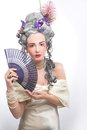 Young lady victotian woman in eighteenth century image posing with fan Stock Photo