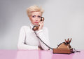 Young lady wearing white turtleneck sweater getting bad news on the phone and crying Stock Photography