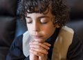 Young latin boy praying latino daily devotional hispanic child and praising god hope in a kid religiuos image Stock Photos