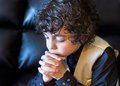 Young latin boy praying latino daily devotional hispanic child and praising god hope in a kid religiuos image Stock Images