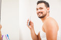 Young Latin man using a nose hair trimmer Royalty Free Stock Photo