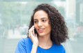 Young latin woman with curly hair at phone in city Royalty Free Stock Photo