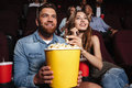 Young laughing couple holding a big popcorn bucket Royalty Free Stock Photo
