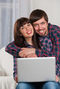 Young laughing couple using laptop while sitting on couch at hom portrait of smiling home Royalty Free Stock Photo