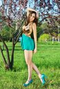 Young leggy brunette in short sexy dress posing near the tree Royalty Free Stock Photos