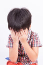 Young little boy crying or playing with hiding face Stock Photo