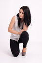 Young long haired black haired woman kneeling holding hair and thinking Royalty Free Stock Photos