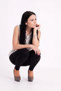 Young long haired black haired woman squatting thoughtful Royalty Free Stock Images