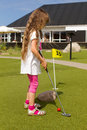 Young long haired girl playing minigolf with hair at course at european holiday resort during summer time Royalty Free Stock Image