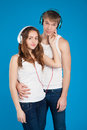 Young love couple boy holding girl wearing headphones listeni listening music in the studio over blue background Stock Image