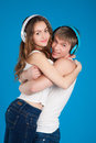 Young love couple boy holding girl wearing headphones listening music studio over blue background Stock Image