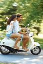 Young love couple enjoying ridding on scooter Stock Photos