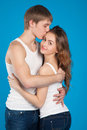 Young love couple holding and kissing each other in the studio over blue background Royalty Free Stock Photo