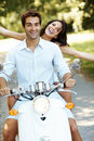 Young love couple on scooter enjoying themselves Royalty Free Stock Photo