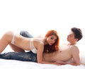 A young and lovely couple laying in lingerie and jeans caucasian erotic the image is isolated on white background Royalty Free Stock Image