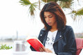 Young lovely woman sitting at coffee shop terrace pensive reading interesting book afro american female enjoying a good or Royalty Free Stock Photography