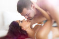 Young lovers kiss kissing in bed Royalty Free Stock Photo