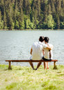 Young lovers sitting on wooden bench with their backs to the camera big lake in front of them Stock Photo