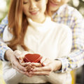 Young loving asian couple holding a heart shaped box together focus on hands Royalty Free Stock Images
